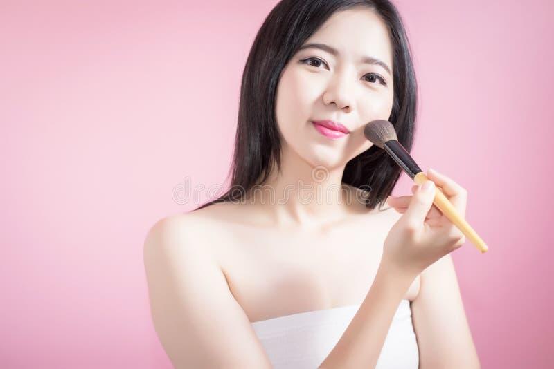 Lange haar Aziatische jonge mooie vrouw die kosmetische poederborstel op vlot die gezicht toepassen over roze achtergrond wordt g royalty-vrije stock foto's