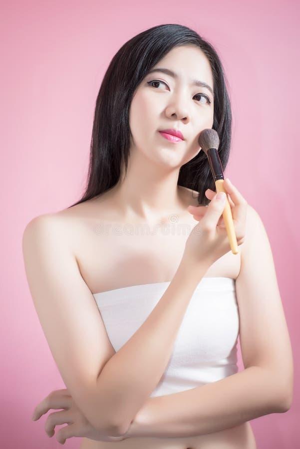Lange haar Aziatische jonge mooie vrouw die kosmetische poederborstel op vlot die gezicht toepassen over roze achtergrond wordt g stock afbeelding