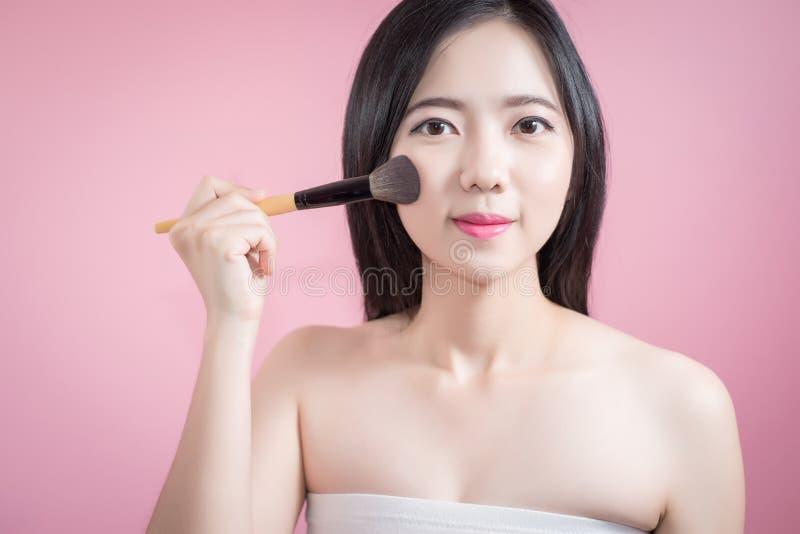 Lange haar Aziatische jonge mooie vrouw die kosmetische poederborstel op vlot gezicht over roze achtergrond toepassen Natuurlijke royalty-vrije stock fotografie