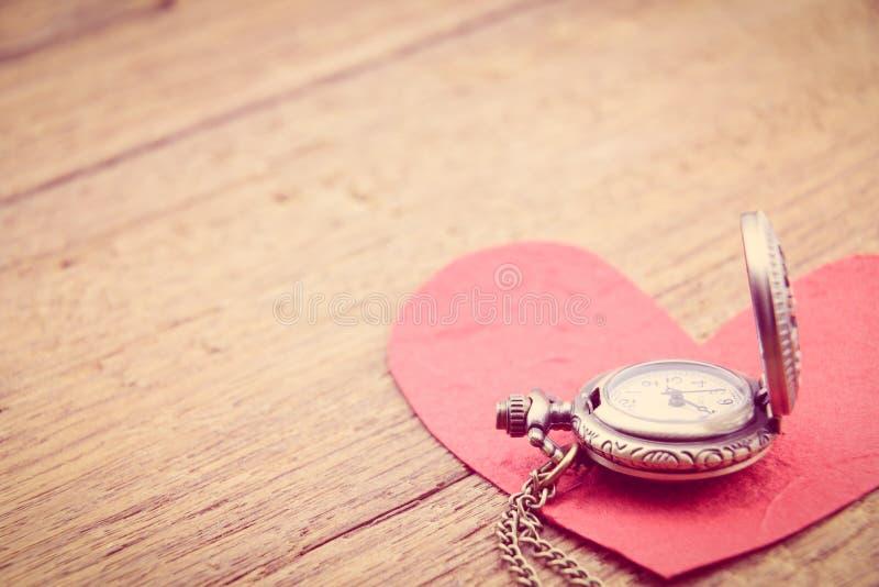 Lange Halskettenantikenart-Taschenuhr mit einem roten Papierherzen lizenzfreie stockfotos