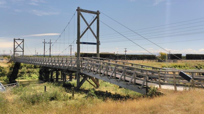 Lange houten die brug door metaaldraden wordt vastgehaakt stock afbeelding