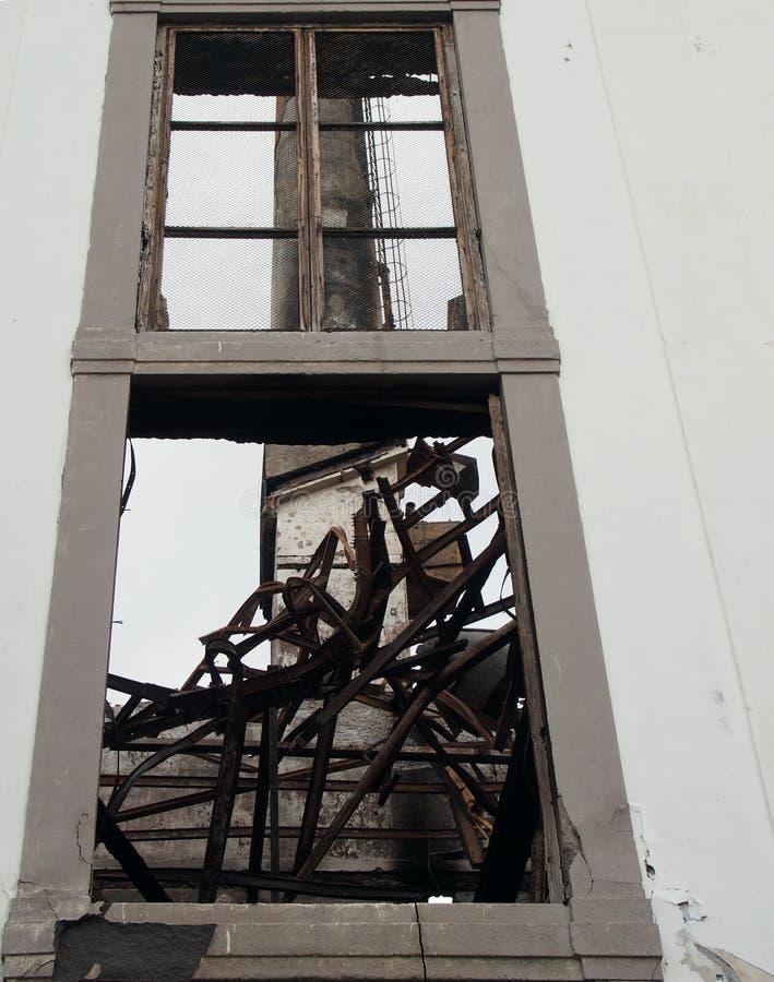 Lange industriële schoorsteen zichtbaar door een gebroken venster van een oude verlaten fabriek met verdraaide balken royalty-vrije stock afbeeldingen