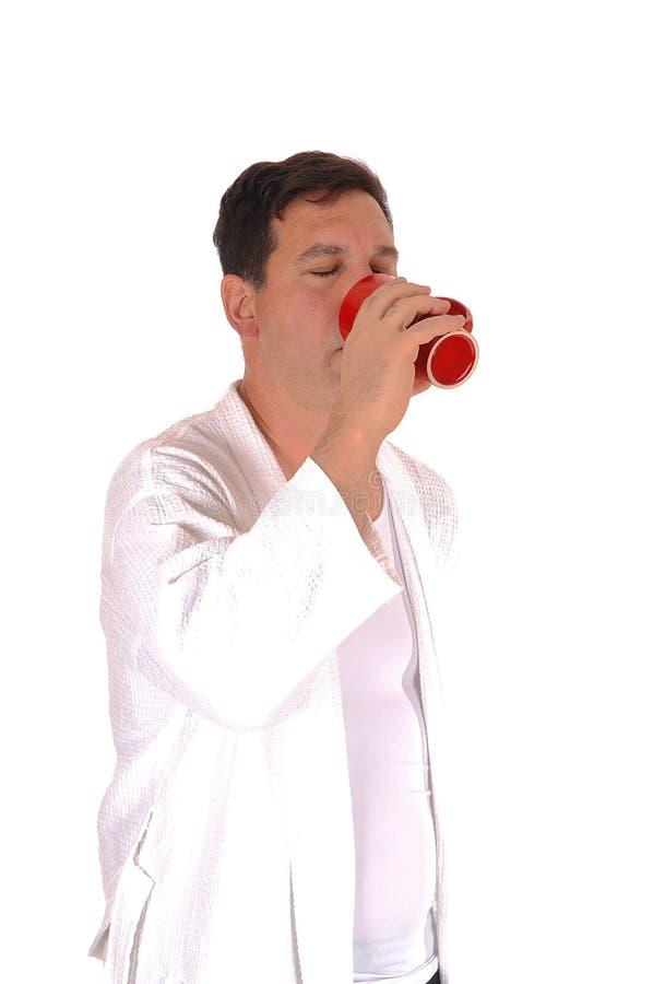 Lange mens die zich in badjas het drinken koffie bevinden stock fotografie