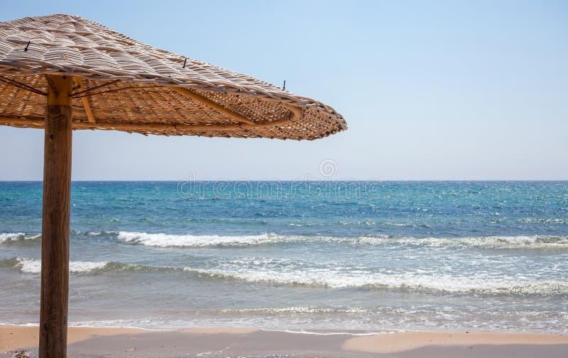 Lange paraplu die zich in het zand bevinden Een houten Bonita-hut die schaduw de oever geven Een heldere zon die boven het overze stock afbeeldingen