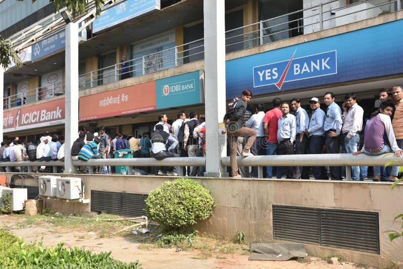 Lange rij van mensen buiten banken om oude 500 en 1000 muntnota's te deponeren en nieuwe munt te krijgen stock afbeelding
