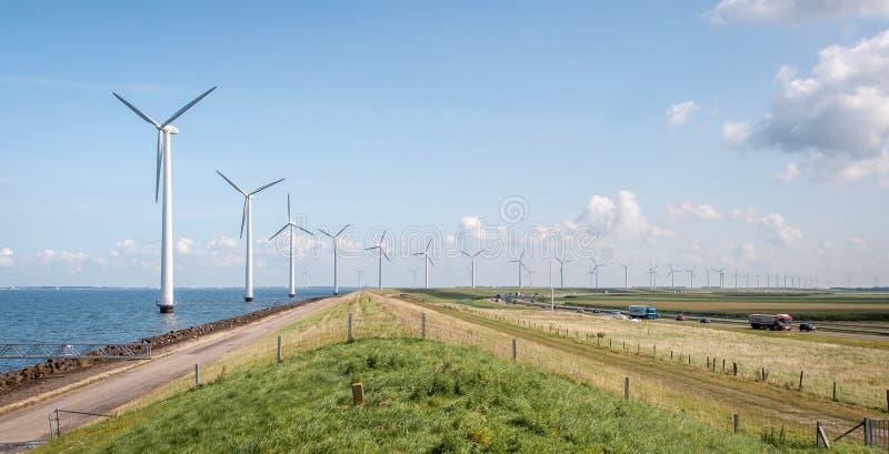Lange rij van windmolens naast de weg, met heel wat verkeer stock fotografie