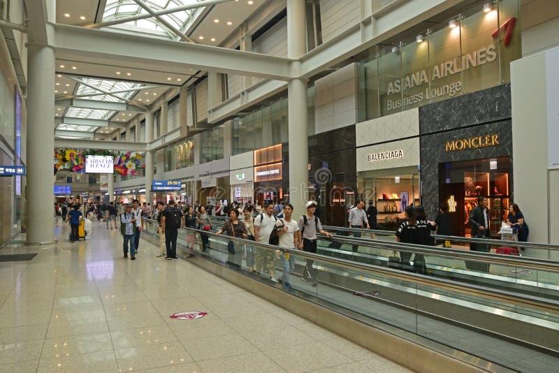 Lange Rolltreppe umgeben durch Luxuseinzelhandelsgeschäfte im koreanischen Flughafen lizenzfreies stockfoto