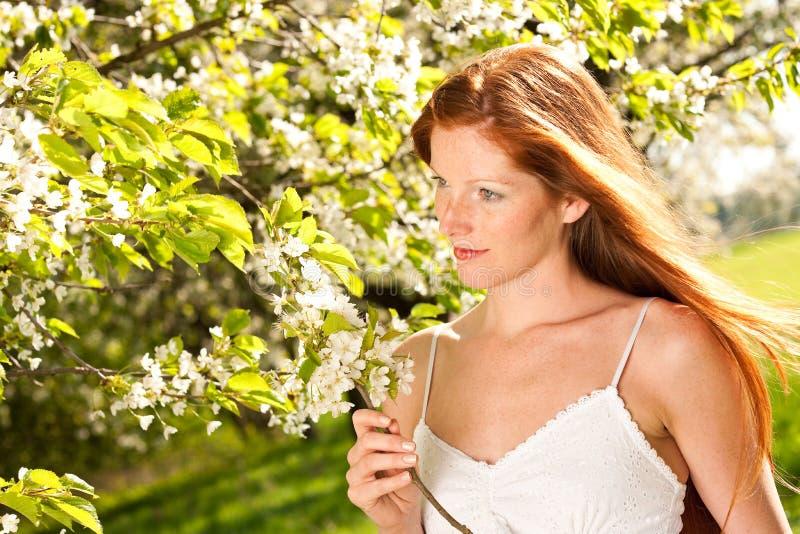 Lange rote Haarfrau, die unter blühendem Baum steht lizenzfreies stockbild