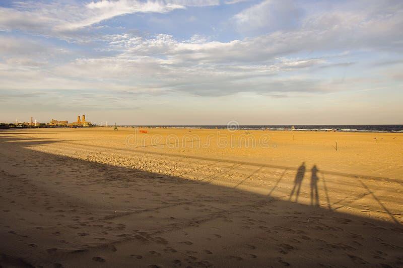 Lange Schaduwen op het Strand stock foto