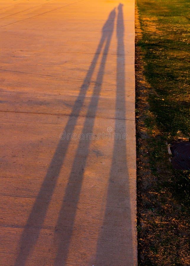 Lange schaduwen van twee mensen bij zonsondergang stock afbeeldingen