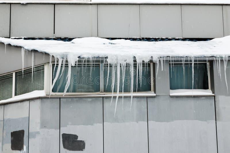 Lange scherpe ijskegels op een dak van een grijs gebouw stock foto's