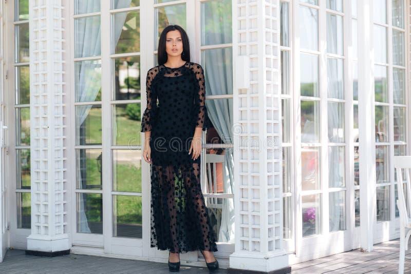 Lange slanke modeltribunes buiten, gekleed in een zwarte nauwsluitende netwerkkleding Stelt op de achtergrond van bevlekt stock foto's