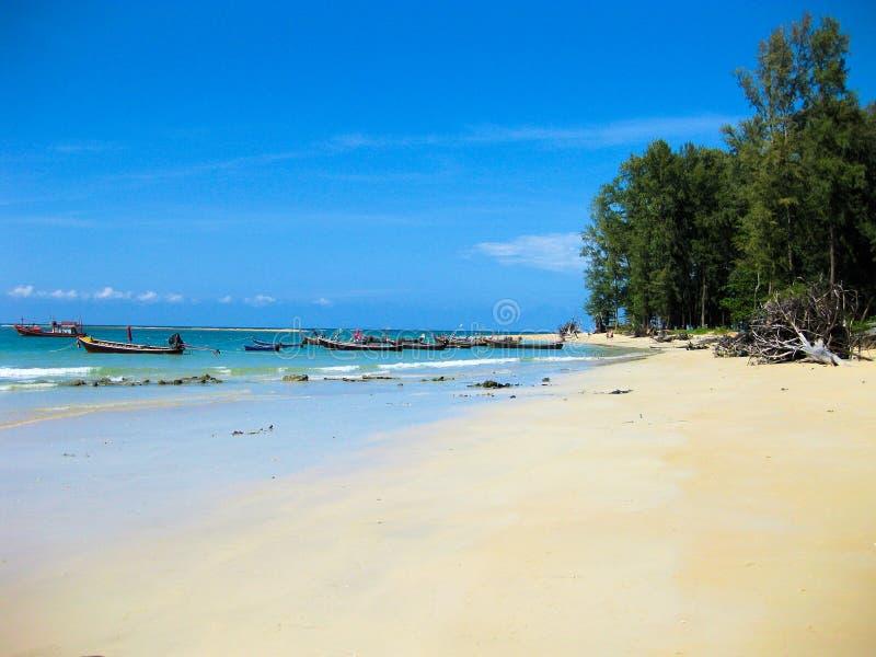 Lange staartboten in een baai tegen blauwe hemel bij Nai Yang-strand dichtbij de luchthaven van Phuket, Thailand stock afbeelding