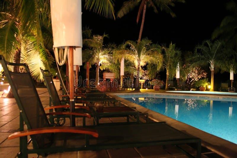 Lange stoelen bij de pool stock fotografie
