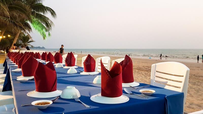 Langer Abendtisch und Stuhl auf dem Sand setzen auf den Strand stockbilder