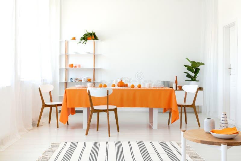 Langer Esszimmertisch bedeckt mit orange Tischdecke und bequemen weißen Stühlen stockfotos