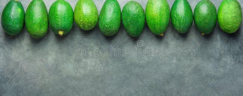 Langer Fahnen-Titel Bündel reife rohe Avocados vereinbart in der oberen Grenze auf dunklem Steinhintergrund Draufsichtkopienraum  lizenzfreie stockfotografie