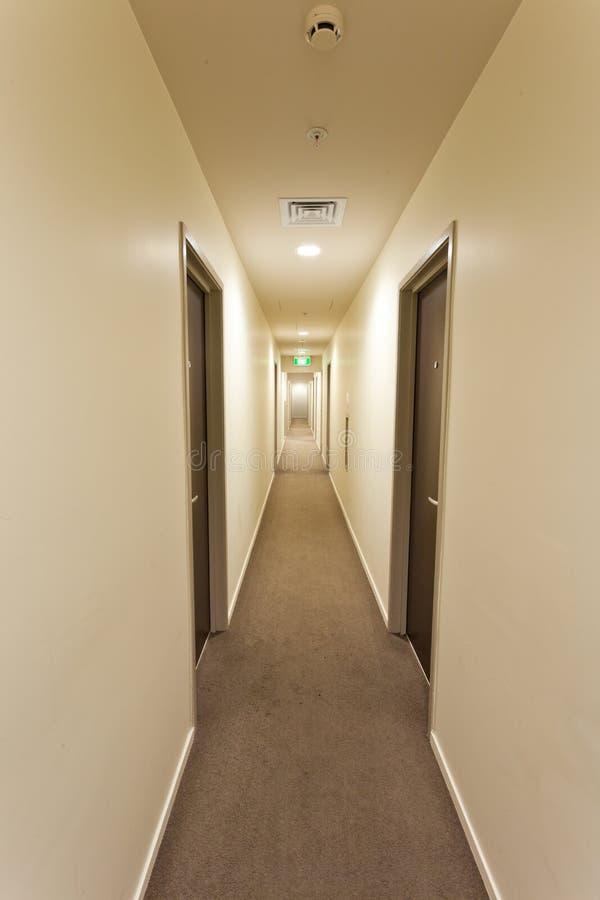 Langer Flur langer flur mit hotelzimmertüren und ausgang kennzeichnen stockbild