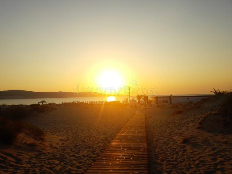 Langer hölzerner Gehweg zum tropischen Strand im Sonnenaufgang lizenzfreies stockbild