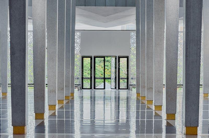 Langer Korridor zwischen vielen Spalten, offene Türen am Ende, symmetrische moderne Halle lizenzfreie stockfotos