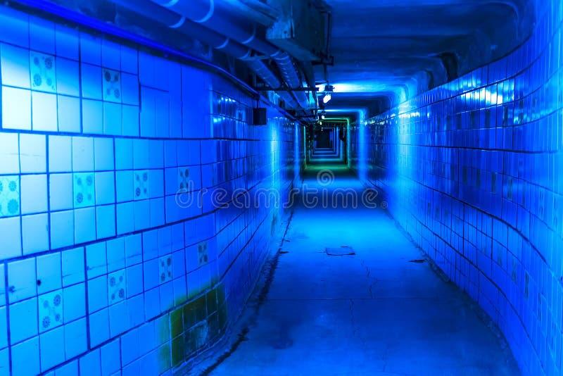 langer leerer Tunnel mit Rohren und Dienstprogrammen auf der Decke, blaue Neonlichter stockfotos