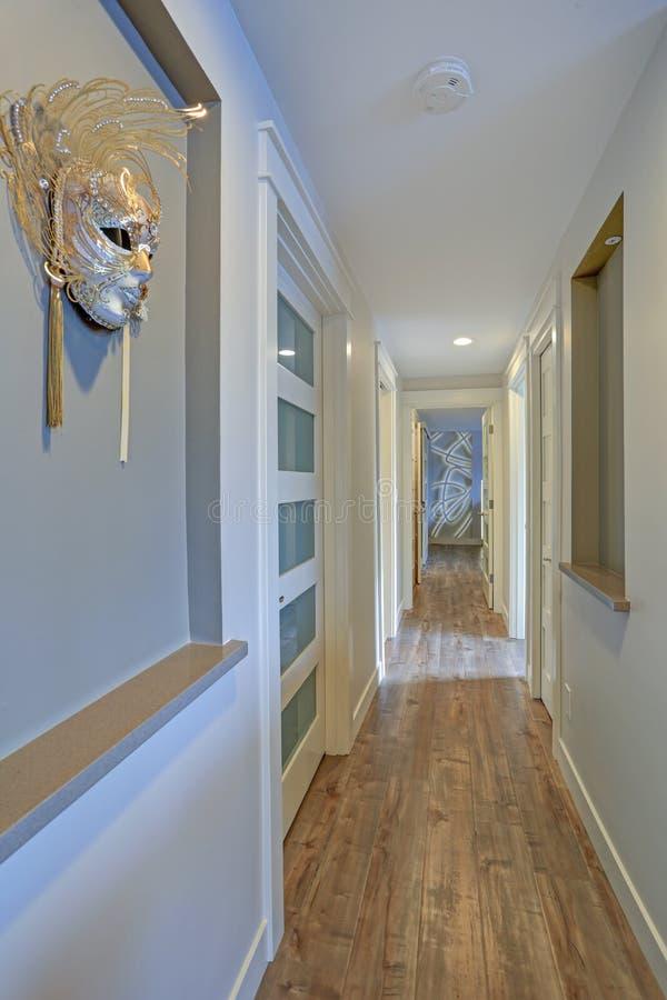 Langer, schmaler Korridor mit dekorativer Wandmaske lizenzfreie stockfotos