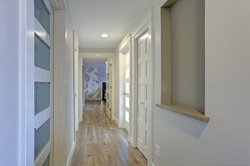 Langer, schmaler Korridor mit den weißen Türen betont mit Glasplatten lizenzfreies stockfoto