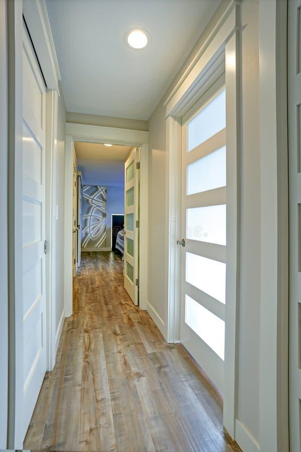 Langer, schmaler Korridor mit den weißen Türen betont mit Glasplatten stockfotografie