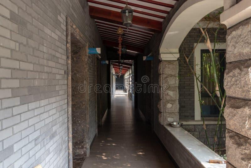 Langer Sommerkorridor des Gebäudes mit offenen Türen Steinfliesenboden, offene Fenster Hängende chinesische Laternen stockbild