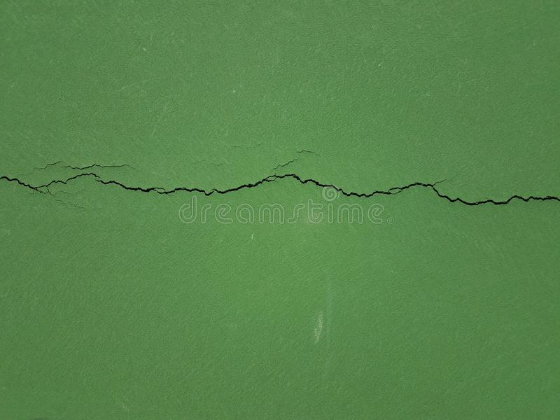 Langer Sprung in geschädigter grüner Oberfläche oder in Boden stockbilder