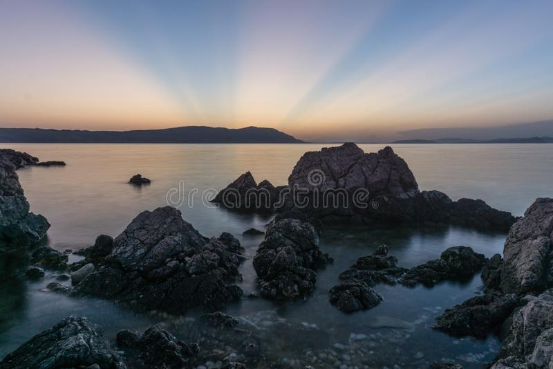 Langes Belichtungsfoto des Wassers durchlaufend Felsen auf dem schönen Sonnenuntergang, Sonne, die hinter Insel geht stockfoto