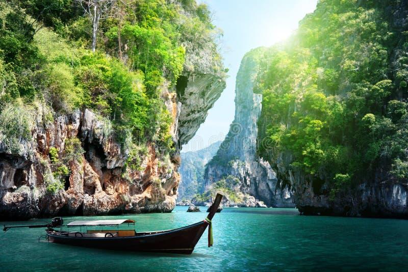 Langes Boot und Felsen auf railay Strand in Thailand stockbild