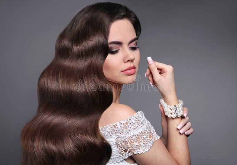 Langes gesundes gewelltes Haar Schöne Frisur Purpurrotes Make-up und bunte helle Nägel Brun stockfotografie
