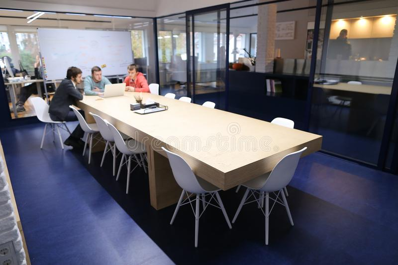 Langes Kabinett mit Tabelle in der Mitte des Arbeitstages mit Leute imm stockfotografie