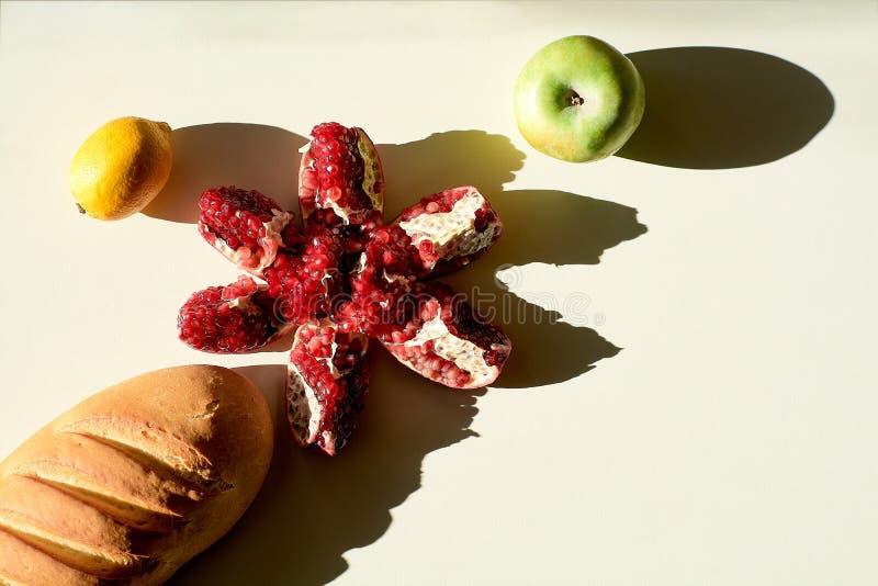 Langes Laib des Brotes und reifer roter saftiger Granatapfel, grüner Apfel, gelbe Zitronenlüge separat auf einem weißen Hintergru lizenzfreie stockfotos