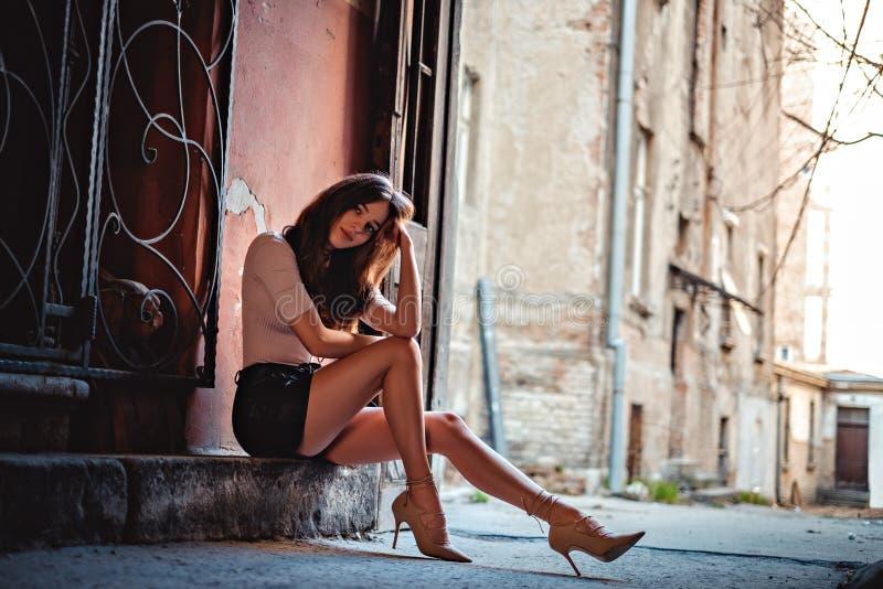 Langes mit Beinen versehenes Mädchen, das auf der Treppe sitzt stockfotografie