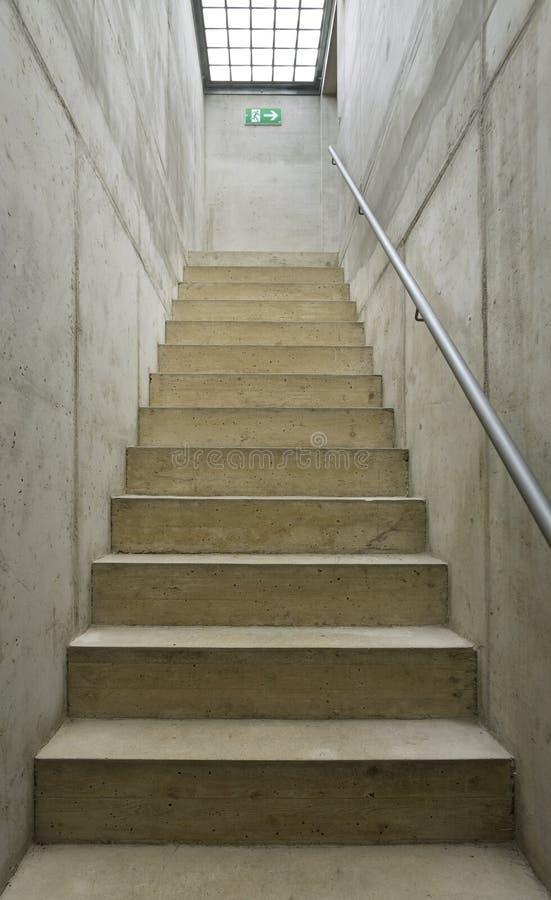 Langes schmales konkretes Treppenhaus stockfotos