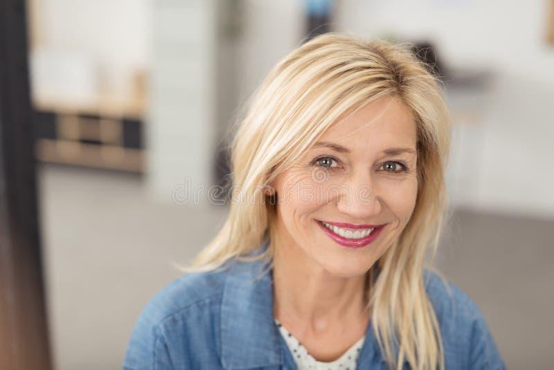 Langhaarige blonde Frau, die an der Kamera lächelt lizenzfreie stockfotos