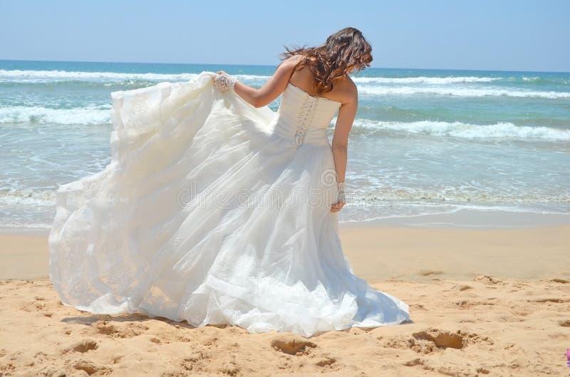 Langhaarige Brunettebraut richtet ihr Kleid gerade, das auf dem Sand, der Strand auf dem Indischen Ozean steht Hochzeit und Flitt lizenzfreies stockfoto