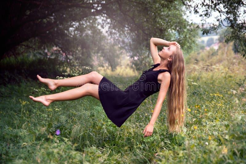 Langhaariges blondes Mädchen, das auf Wiese frei schwebt lizenzfreies stockbild