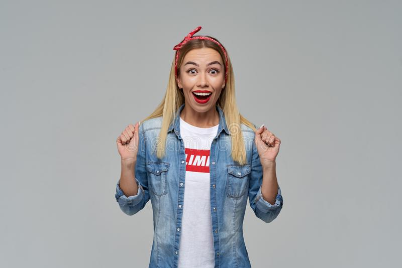 Langhaariges blondes Studentenmädchen glaubt nicht ihren Augen mit Glück-, entsetztem und frohemgesichtsausdruck stockbilder