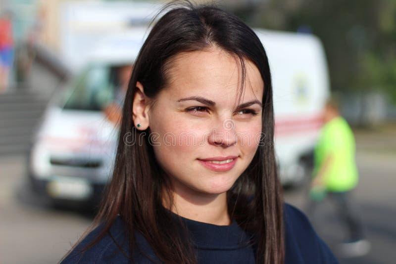 langhaariges brunette Mädchen, das im Quadrat auf dem Hintergrund eines Krankenwagens lächelt Porträt der europäischen Frau im bl stockfoto