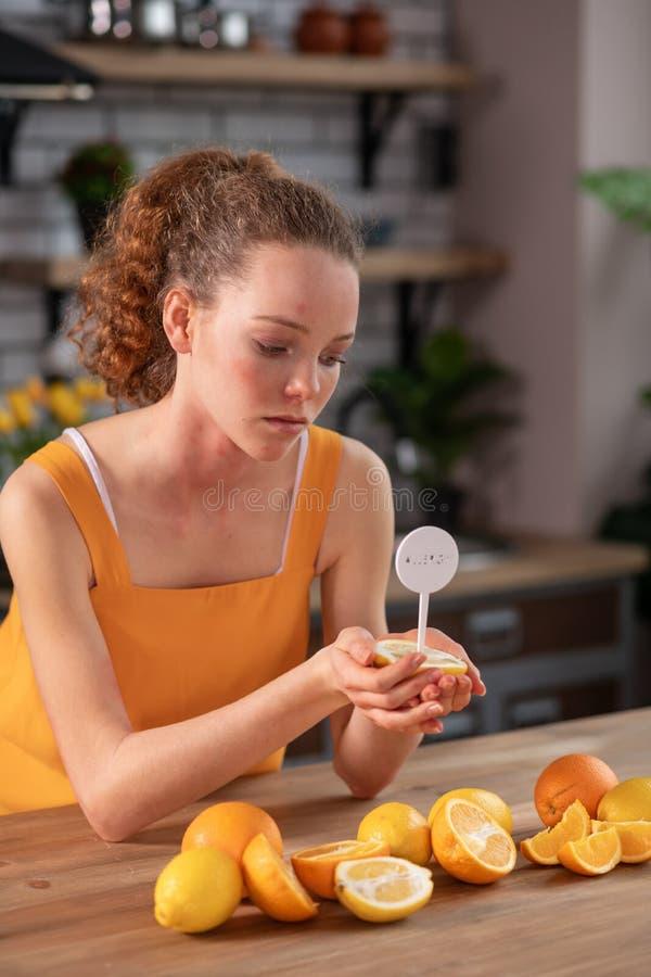 Langhaariges gelocktes Mädchen, das halb von der Zitrone mit Mitteilungsstock herein trägt stockfoto