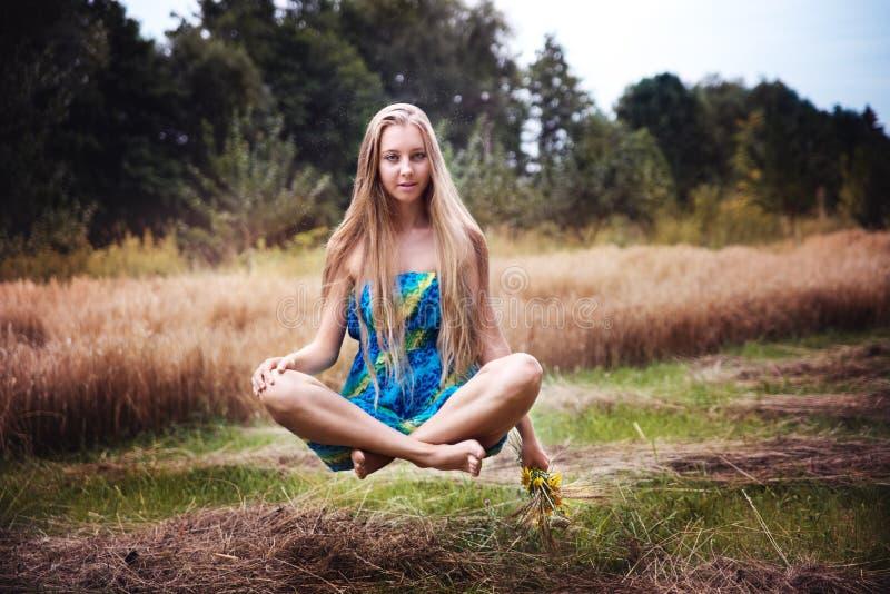 Langhaariges Mädchen, das über Feld frei schwebt stockfoto