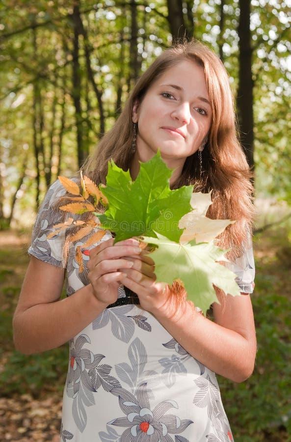 Langhaariges Mädchen mit Ahornholzblatt lizenzfreie stockfotos