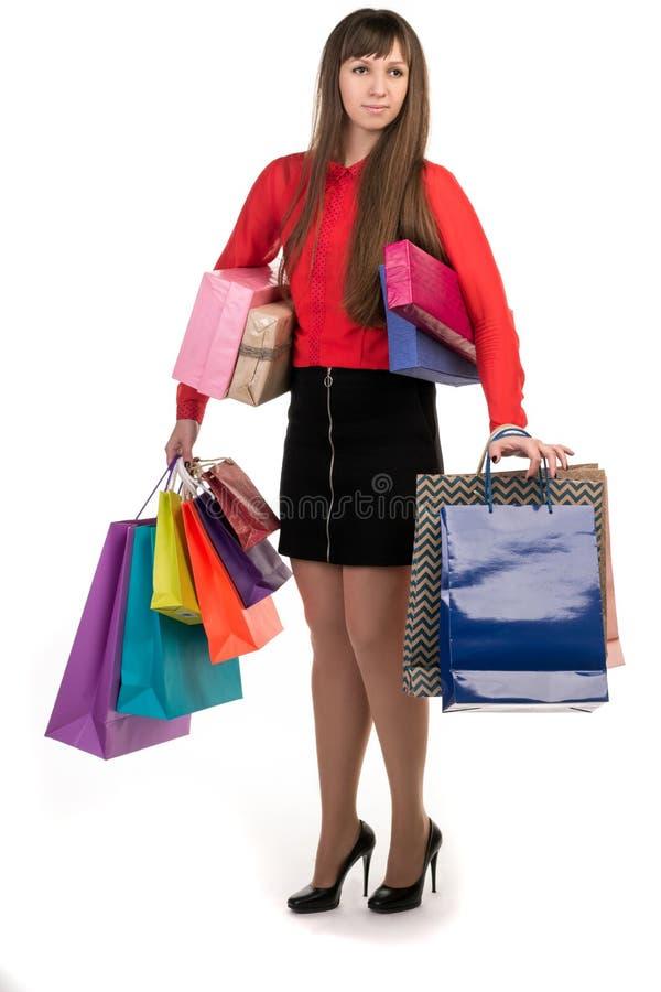 Langhaariges Mädchen steht mit vielen buntes Einkaufspapier packa stockbild