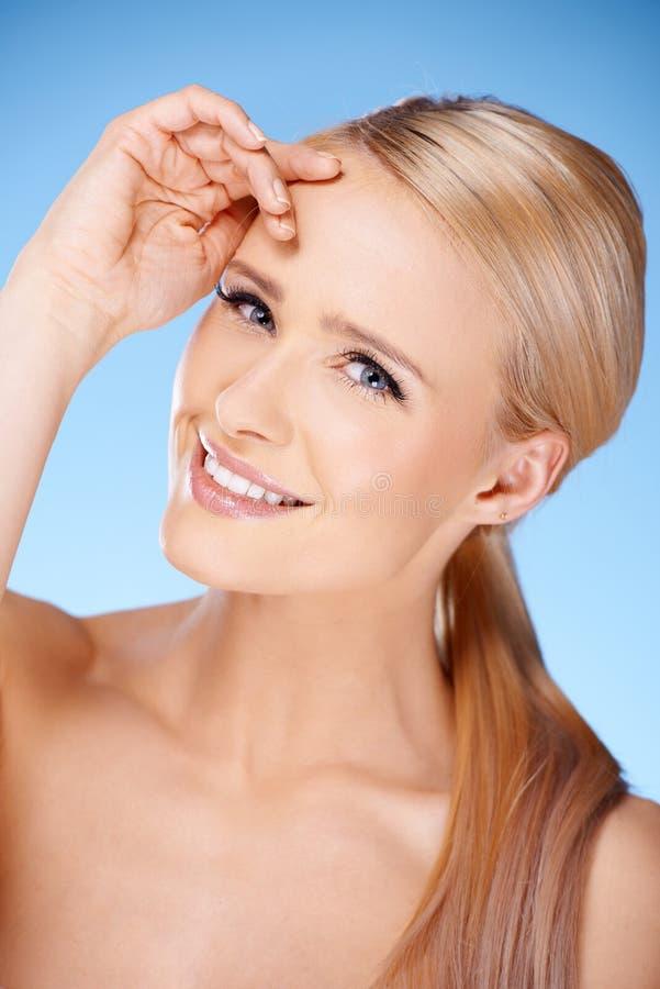 Langharig blond vrouwenportret op blauw stock foto