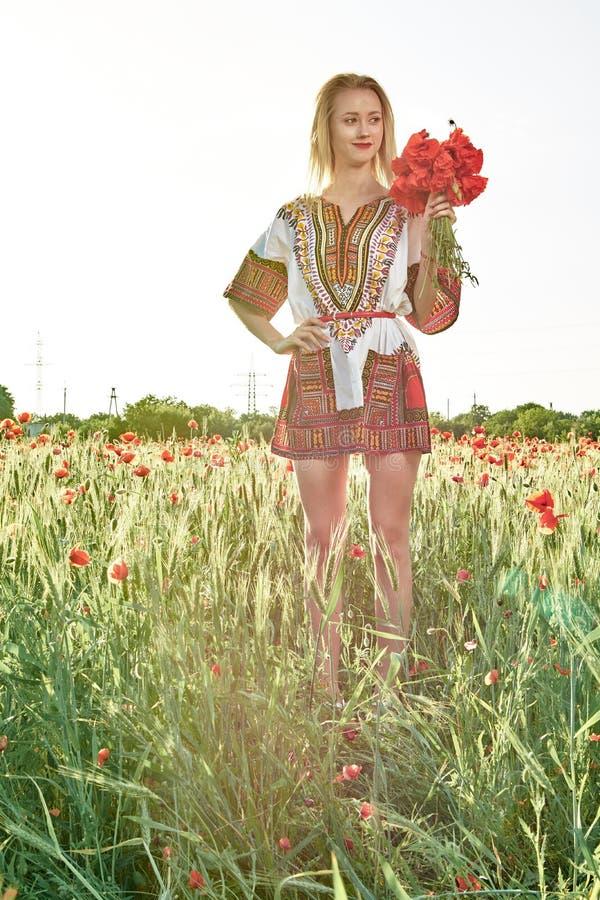 Langharig blonde jonge vrouw in een witte korte kleding op een gebied van groene tarwe en wilde papavers royalty-vrije stock fotografie
