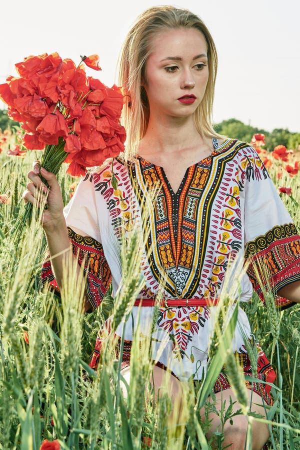 Langharig blonde jonge vrouw in een witte korte kleding op een gebied van groene tarwe en wilde papavers royalty-vrije stock foto's
