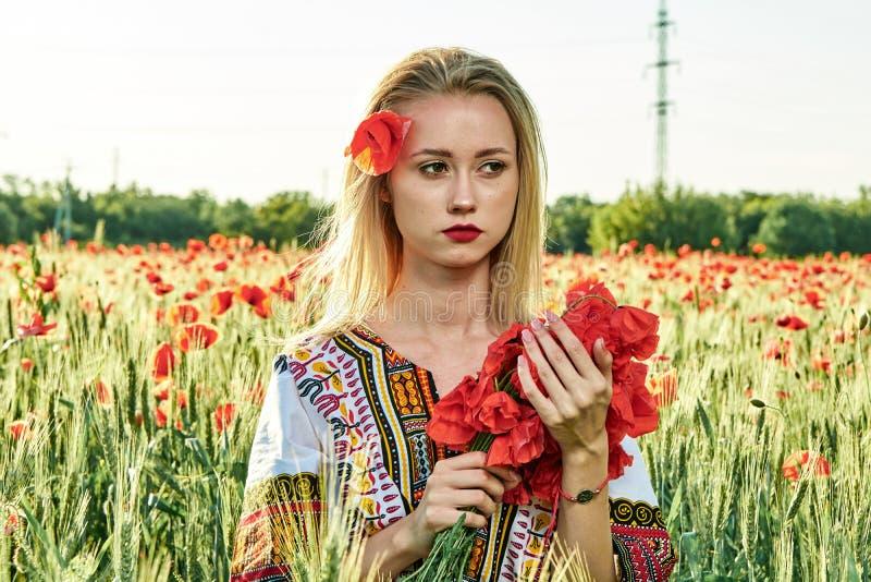 Langharig blonde jonge vrouw in een witte korte kleding op een gebied van groene tarwe en wilde papavers stock fotografie